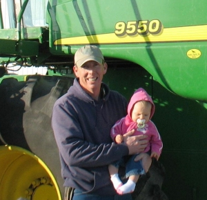 Leland Uden poses with his daughter on his farm.